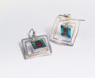 PALAVA- These earrings cannot miss. They are a combination of tasteful style and youthful energy. Double frames of sterling silver are hand-forged to house exclusive organic mobile inlaid mosaics.  ¾ in X 1 ¼      retail   $125