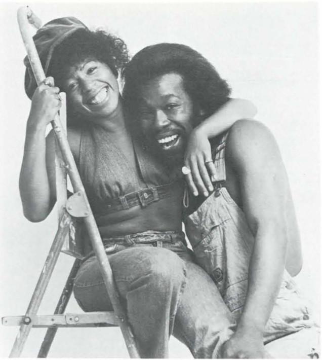 Nick Ashford & Valerie Simpson hugging eachother; Valerie sits on a ladder