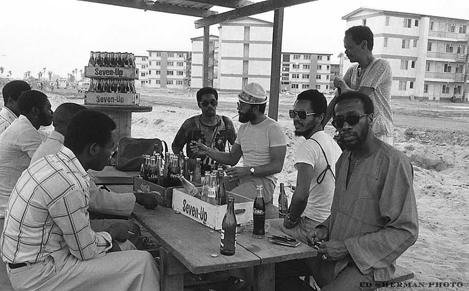 Festac '77 Village Lagos, Federal Republic of Nigeria -West Africa - 2nd World Festival of Art & Culture, Lagos, Nigeria (January, 1977), Photo by Edward Sherman l to r..artists /Reggie Jackson...Nelson Stevens...Napoleon Jones Henderson Ademola Olugebefola...standing is musician Nadi Quamar, seated opposite us are unidentified Nigerians.