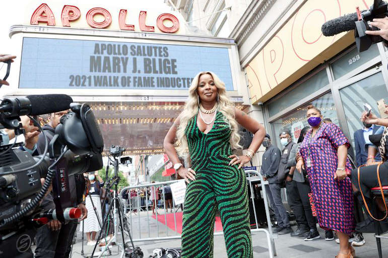 Mary J. Blige stands in front of the Famous Apollo Theater Marquee before she is inducted in The Apollo 'Walk of Fame'. Photo Seitu Oronde